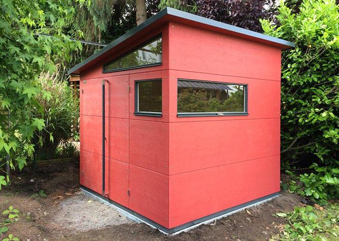 Rotes Gartenhaus mit drei Eckfenstern