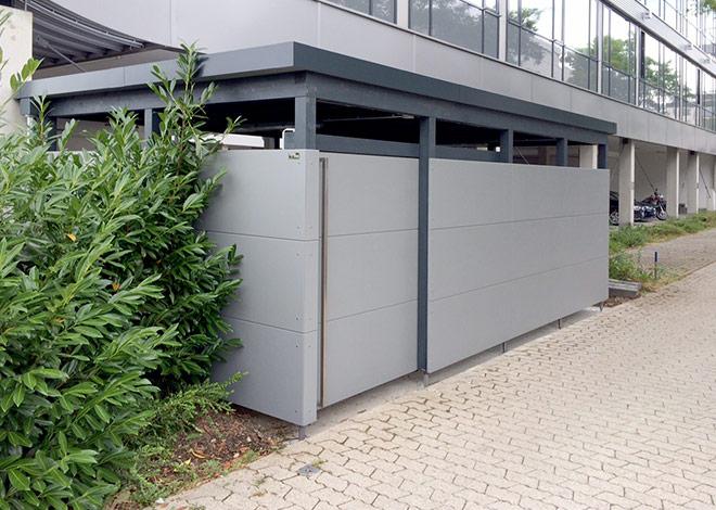 Mülleinhausung vor modernem Bürogebäude